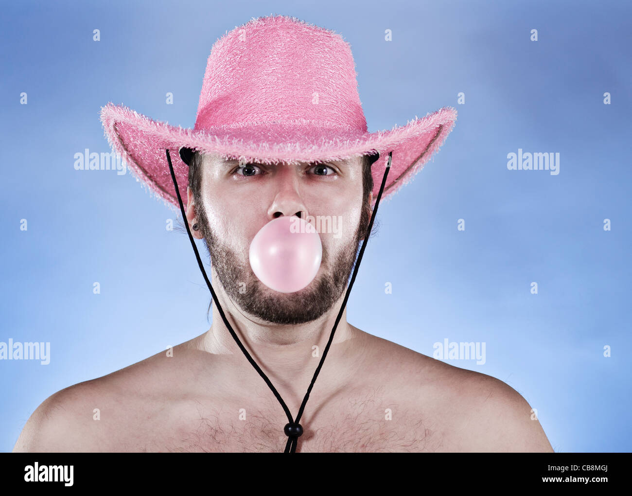 Funny cowboy in pink cowboy hat blowing ping ball of chewing gum ... 7b64170799c