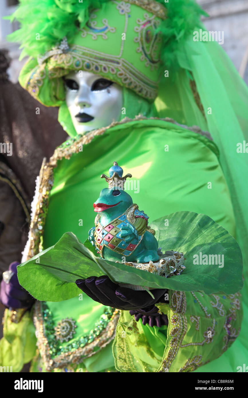 Unidentified participant wear traditional mask and costume during famous Venetian Carnival. - Stock Image