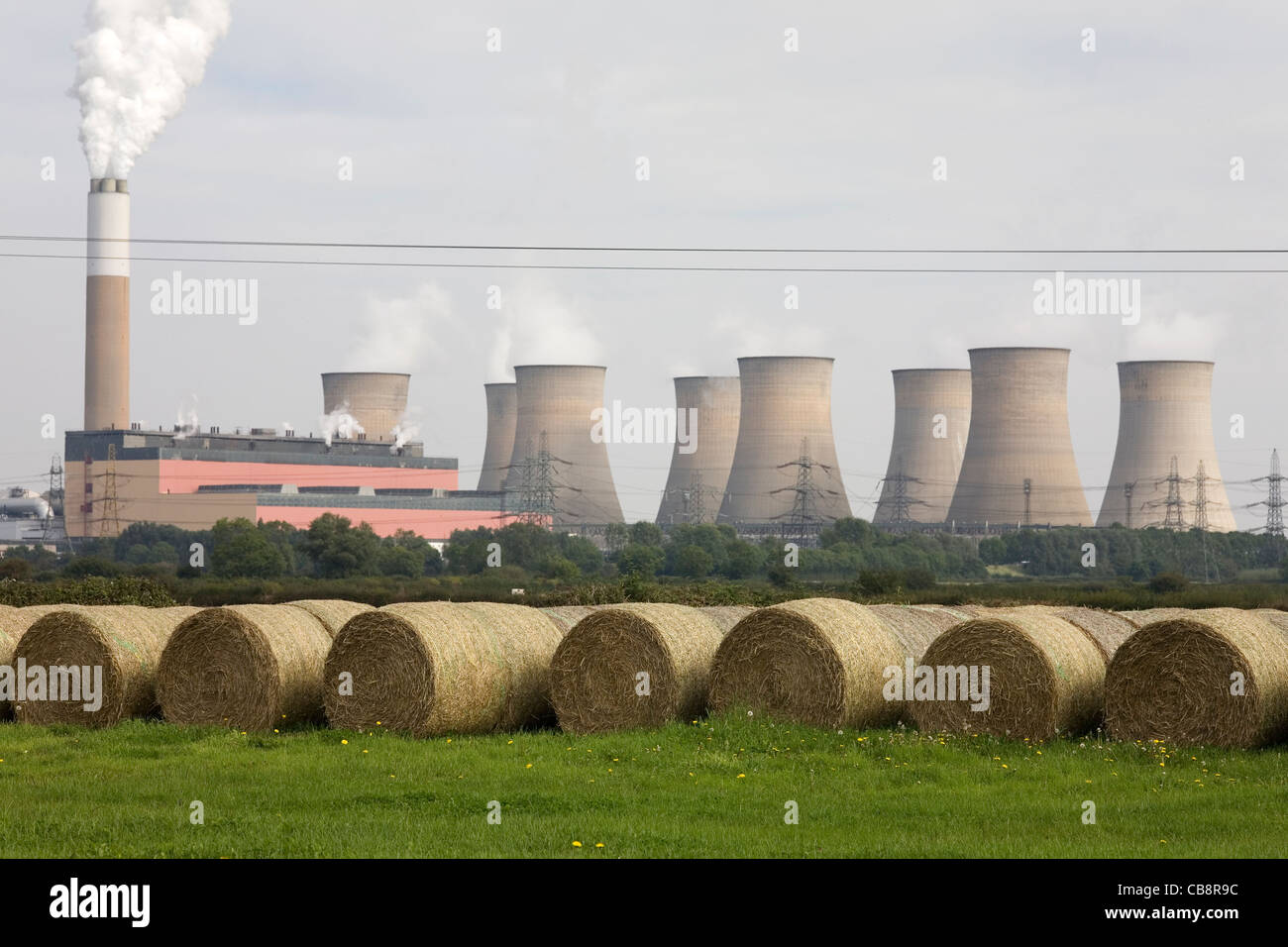 Cottam Power Station Cooling Towers viewed over Round Hay Bales in Summer Field - Stock Image