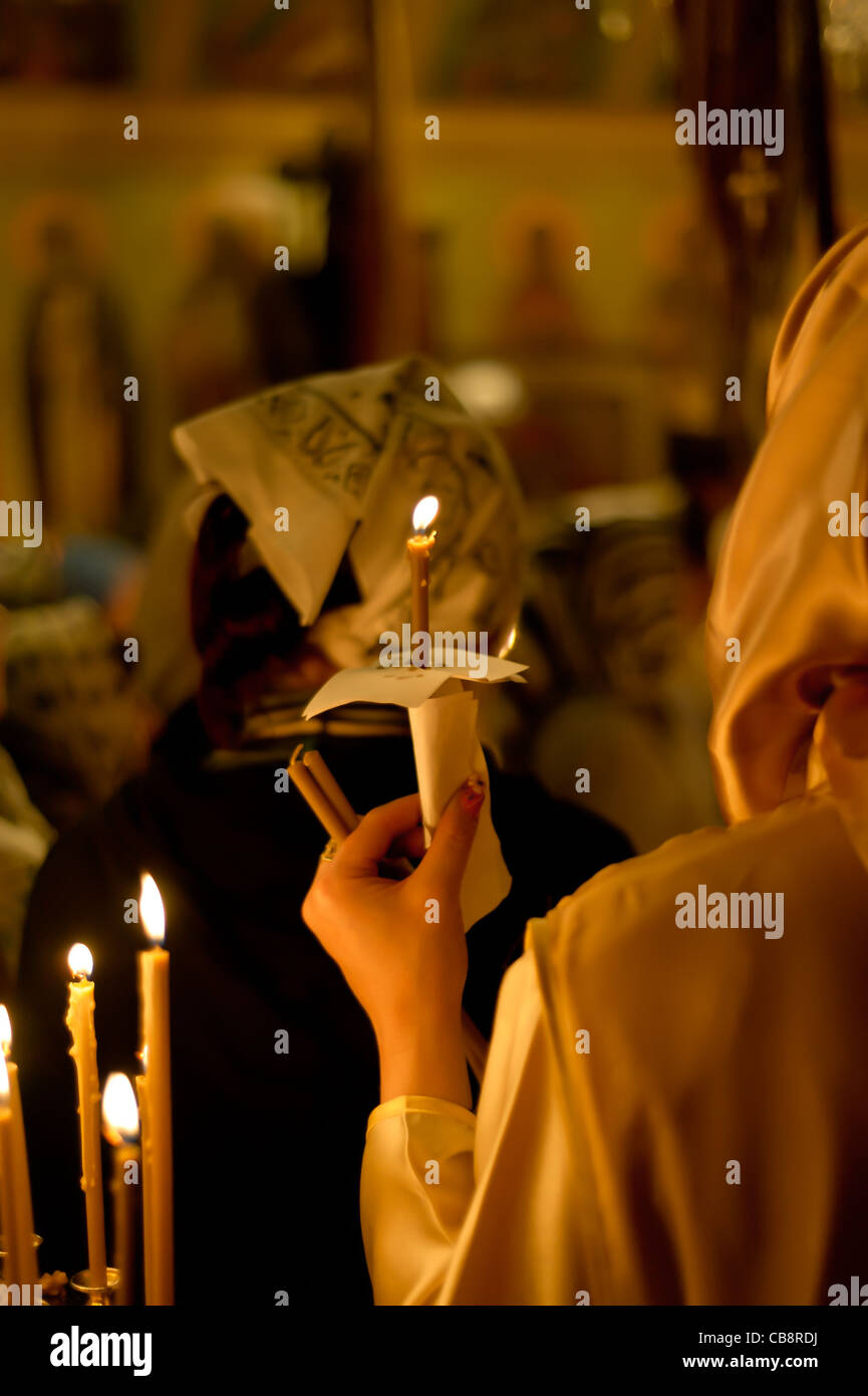 Woman with candle in a church - Stock Image