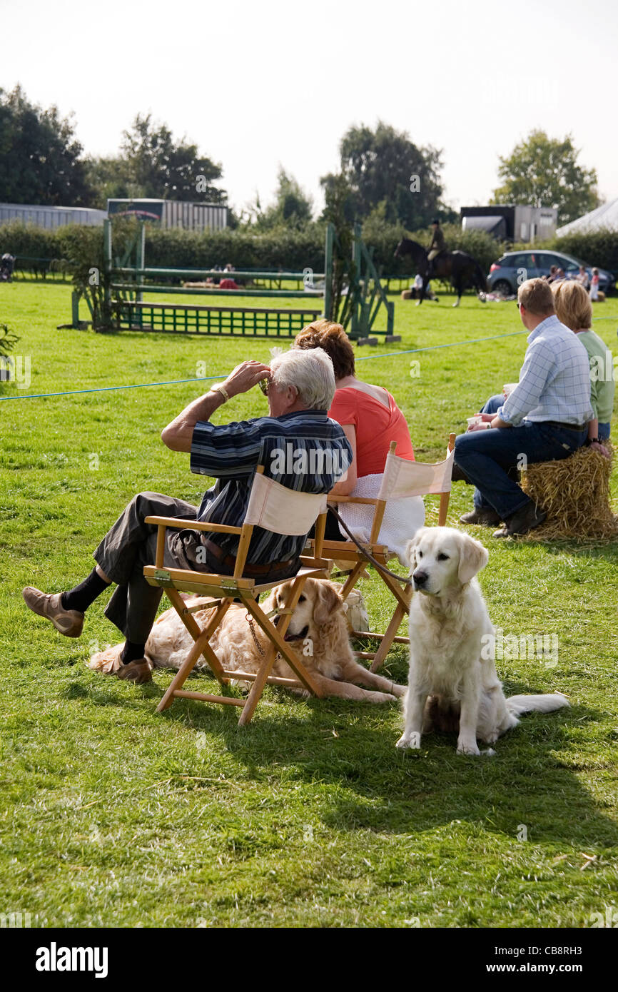 Couples with Golden Retriever Dogs Watch a Show-jumping Class at an Agricultural Show - Stock Image