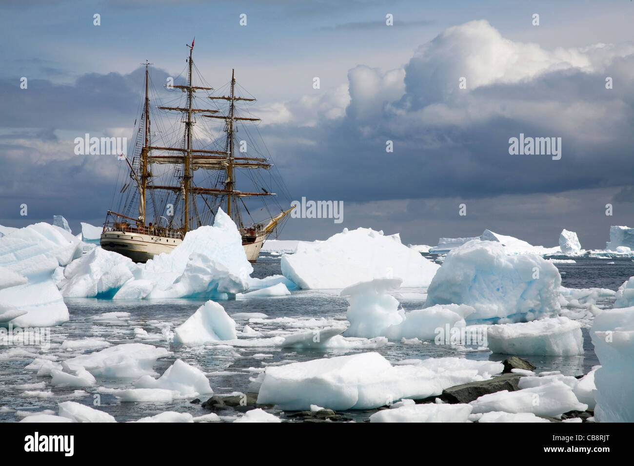 Icebergs and the sailing ship Europa, a three-masted barque, at Port Charcot, Wilhelm Archipel, Antarctica - Stock Image