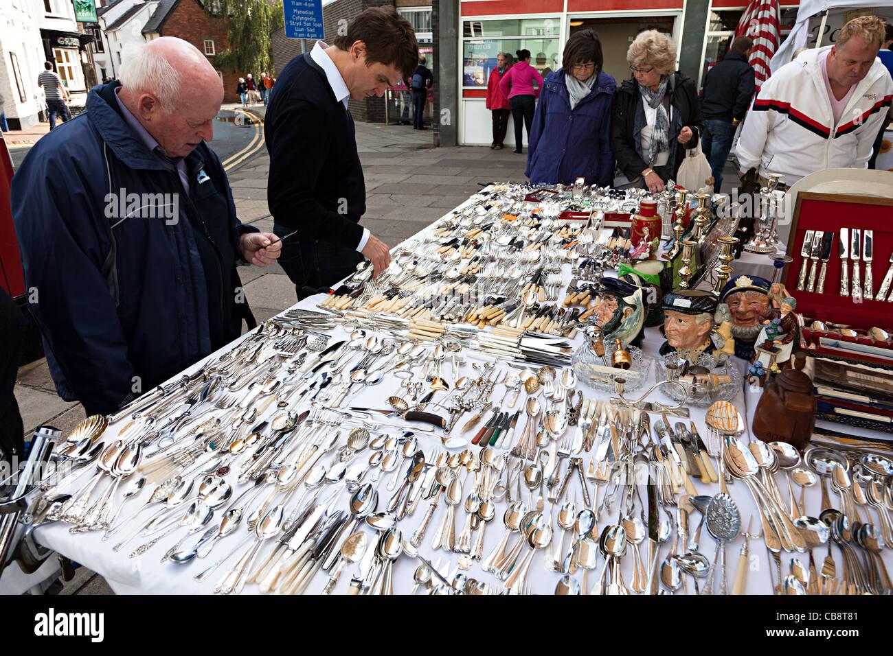 People buying antique bone handled cutlery on sale at market stall Abergavenny Wales UK - Stock Image