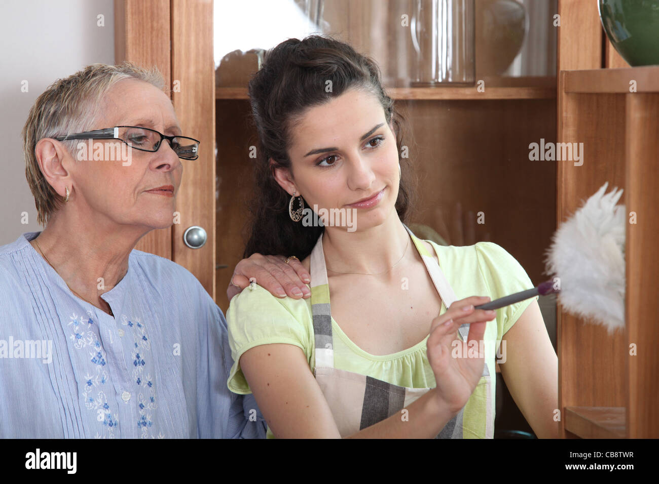 young woman helping senior lady with the cleaning - Stock Image