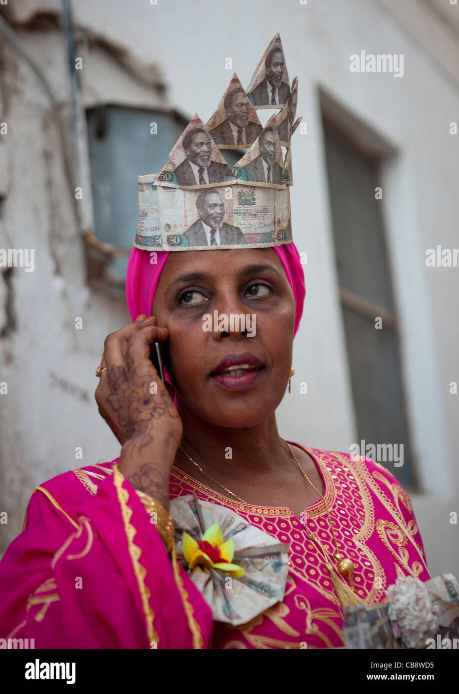 Woman Calling With Cellphone, Wearing Banknotes Hat In Maulidi Festival, Lamu, Kenya Stock Photo
