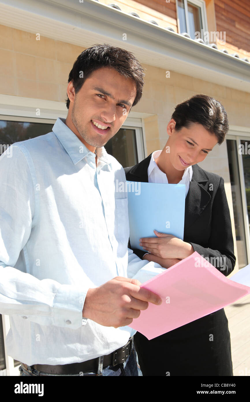 Realty promoters standing in front of a house - Stock Image