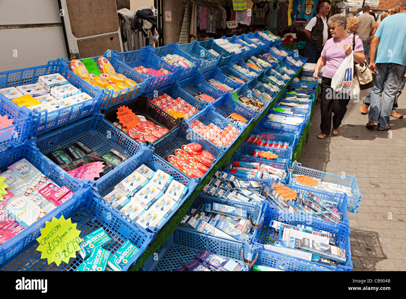 Plastic crates with cheap goods on sale in outdoor market Abergavenny Wales UK - Stock Image