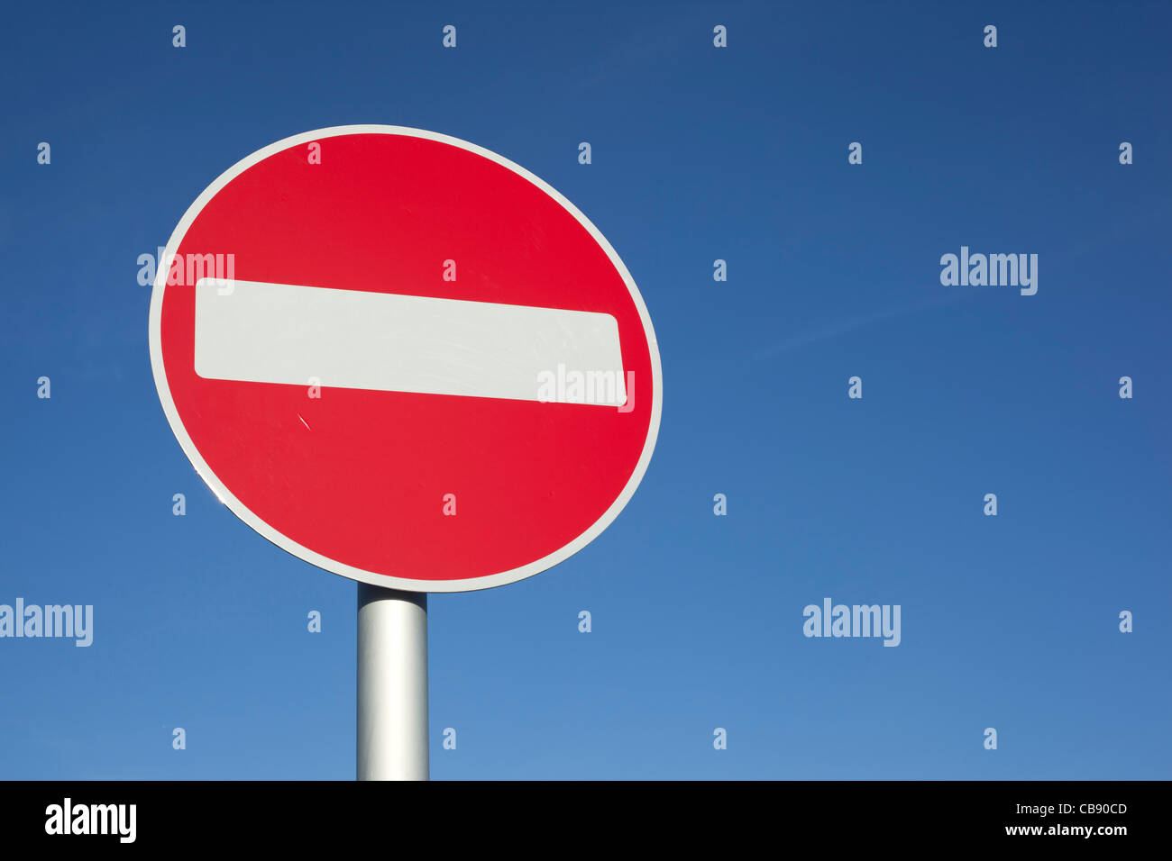 British no entry red and white round road sign and blue sky. - Stock Image