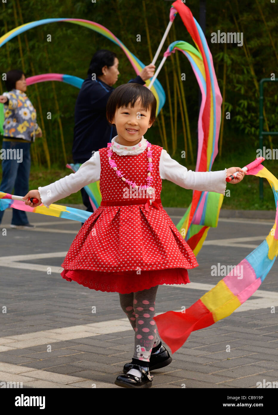 Happy young Chinese girl waving streamers at Zizhuyuan Purple Bamboo Park Beijing Peoples Republic of China - Stock Image