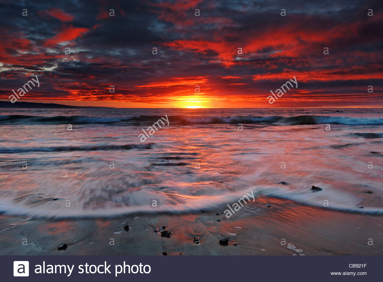 Water racing over ripples on the beach at New Zealand's Molyneux Bay catch some of the fiery color of the sunrise. - Stock Image