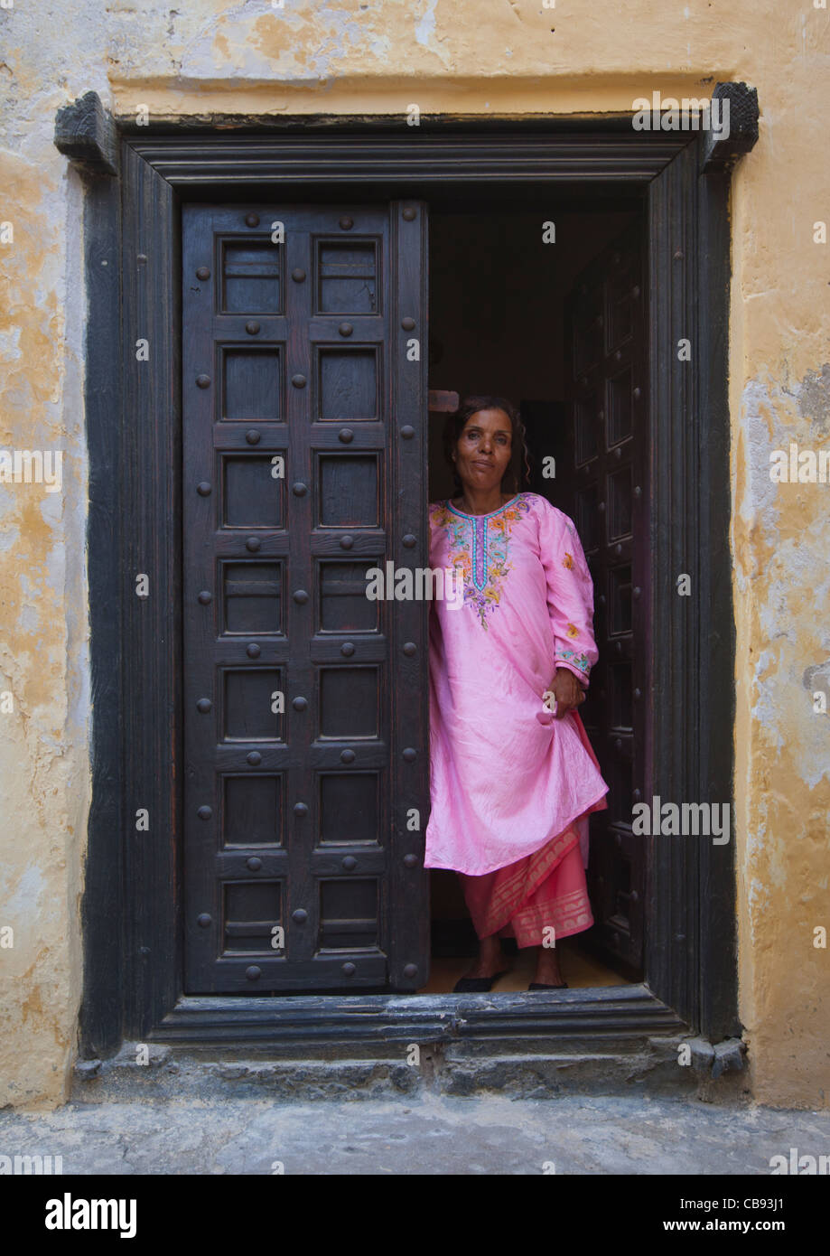 Woman Standing In The Frame Of Omani Wooden Carved Door, Lamu, Kenya Stock Photo
