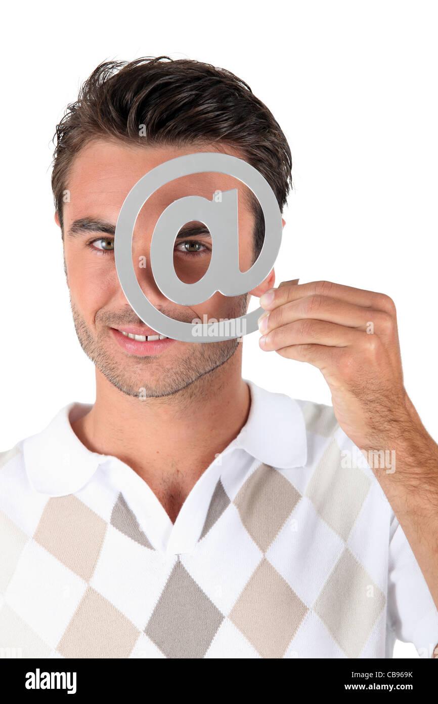 Man holding metallic at symbol over eye - Stock Image