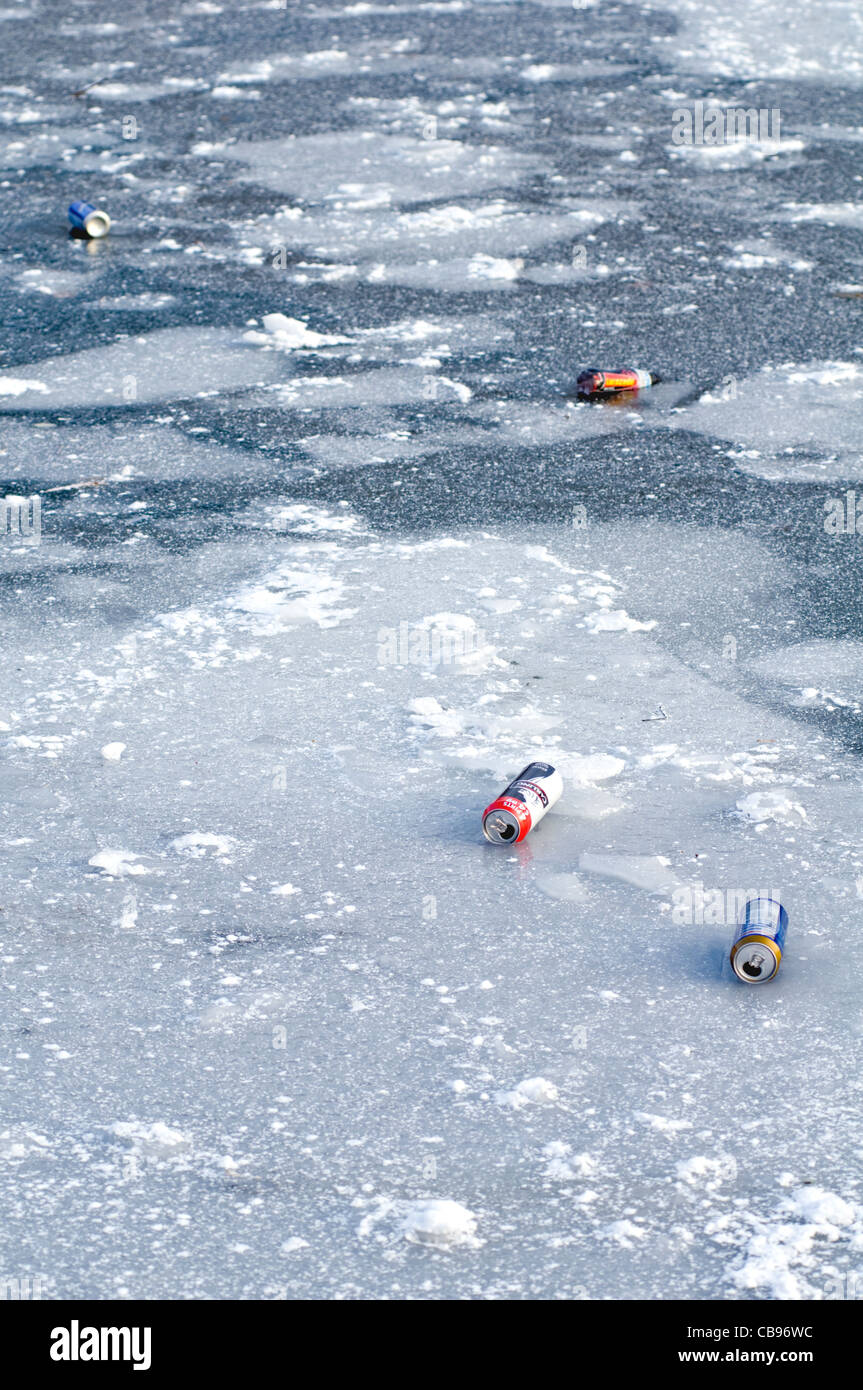 Discarded empty beer cans polluting a frozen waterway in Manchester, England - Stock Image