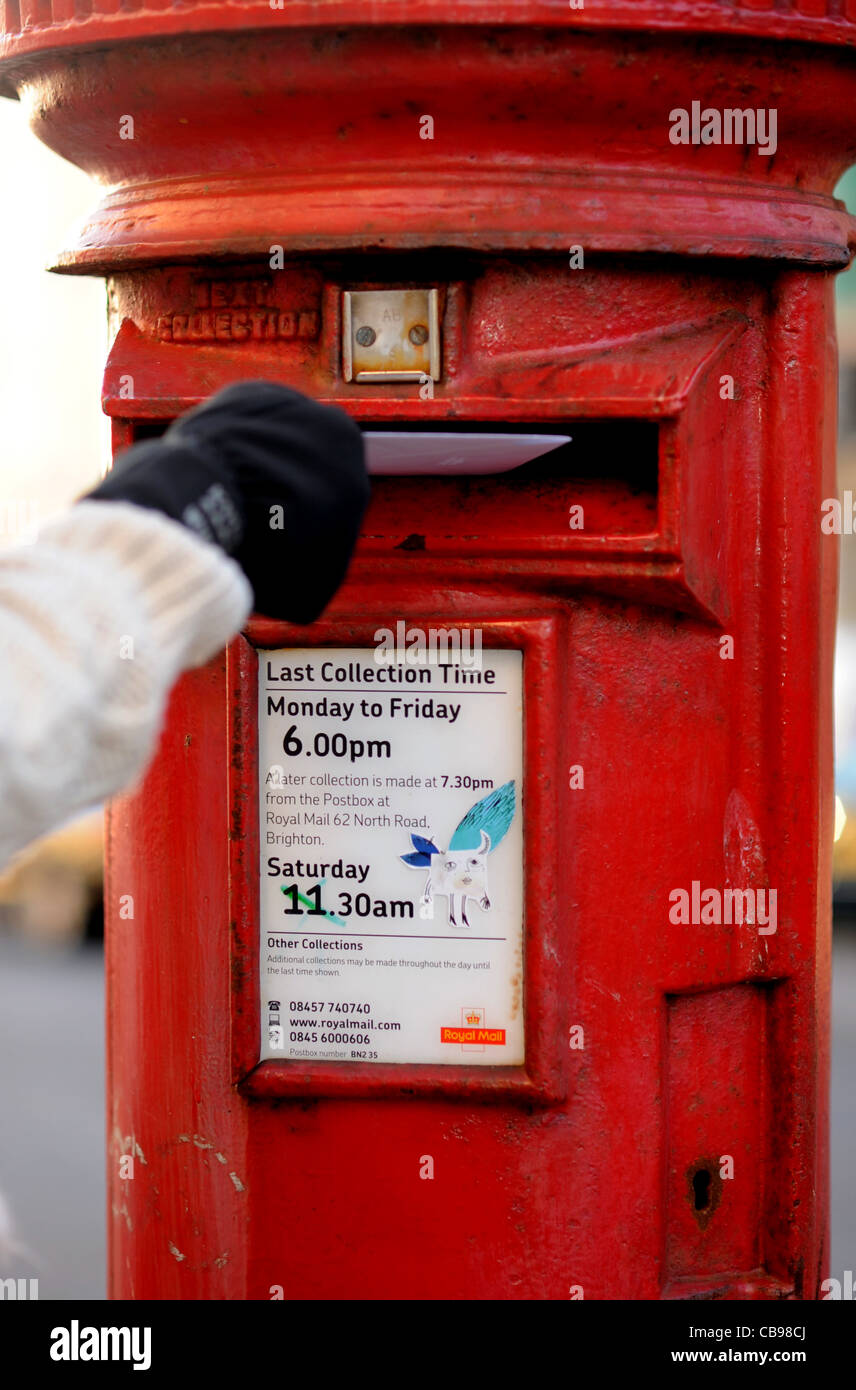 Posting a Christmas card in British red post box in time UK Stock ...