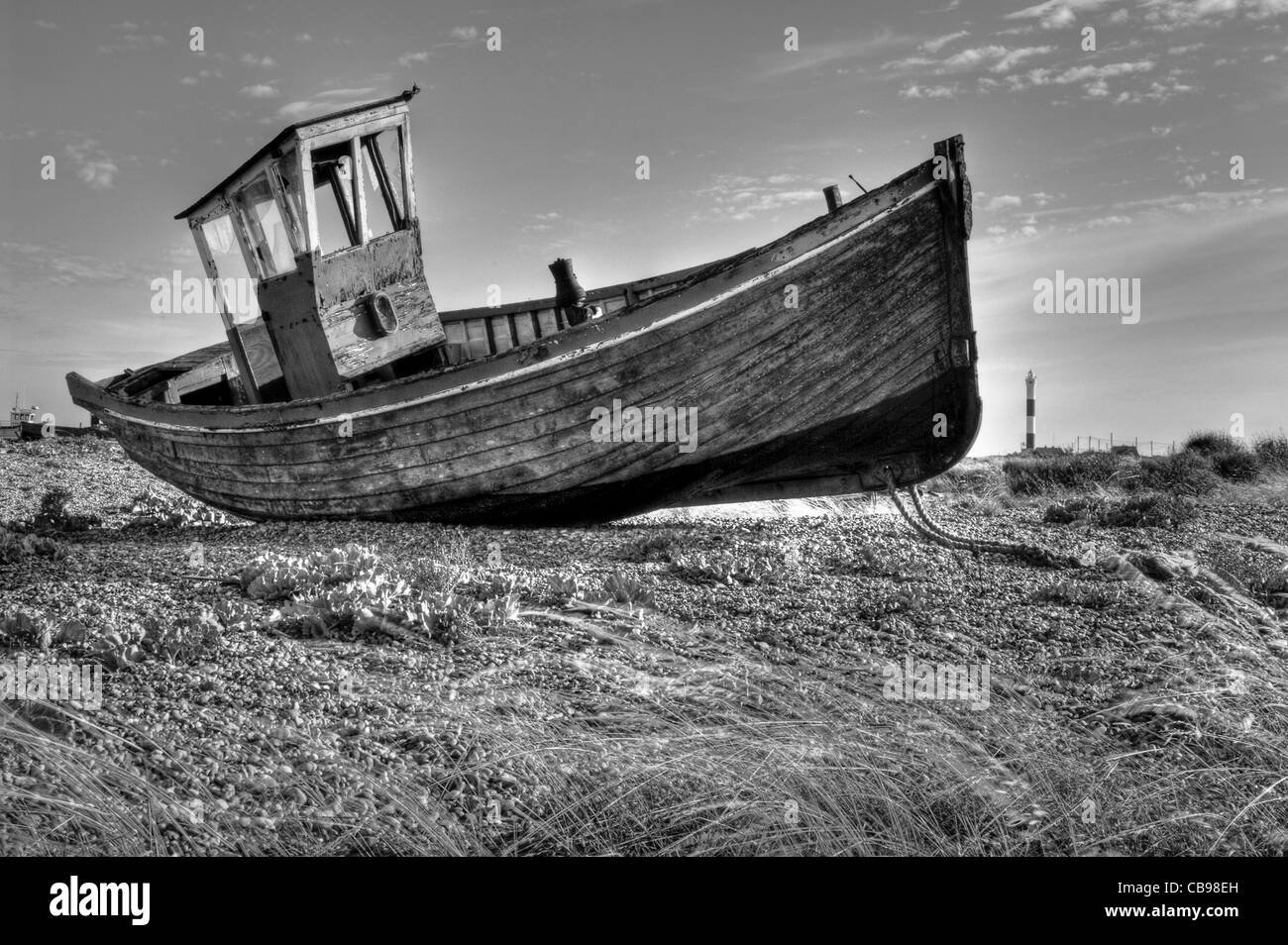 An old abandoned fishing boat on the beach at Dungeness, Kent, UK. The Dungeness lighthouse is in the background. Stock Photo