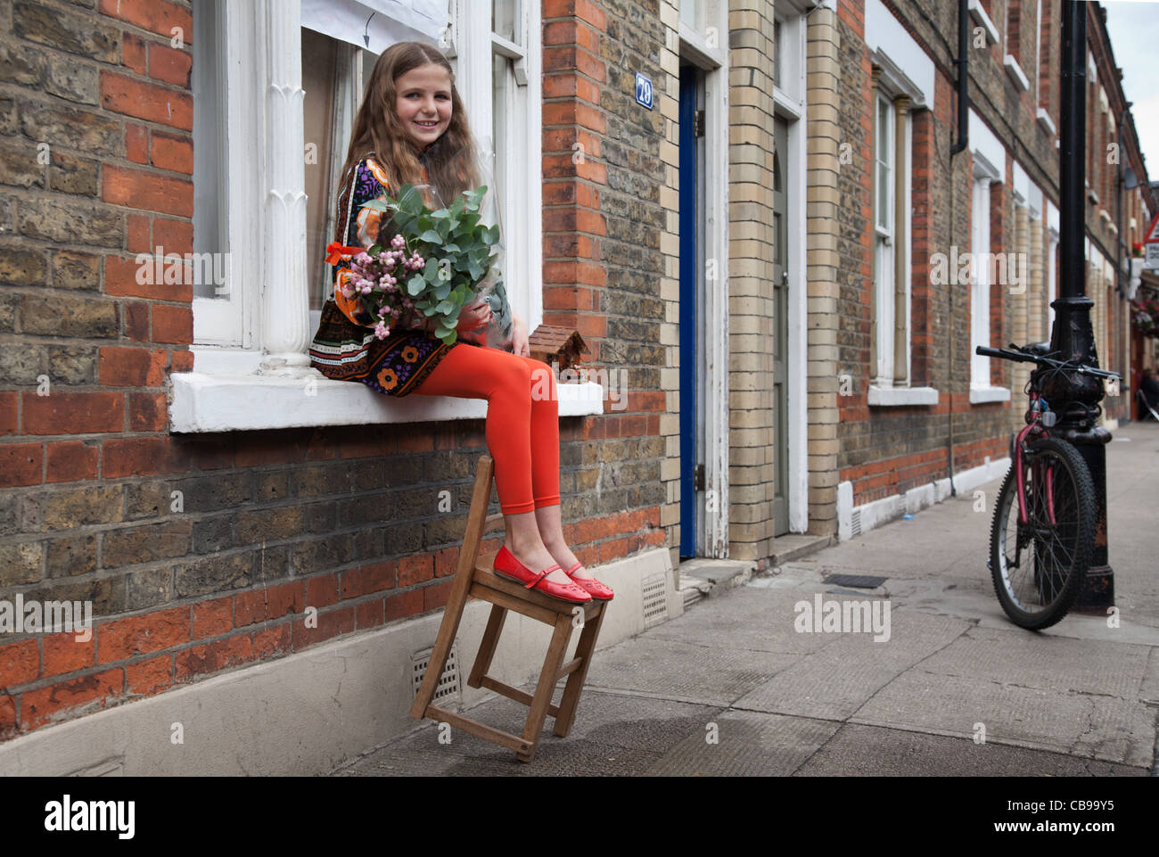 A girl sitting in a windowsill holding a bouquet, Columbia Market, London, UK - Stock Image
