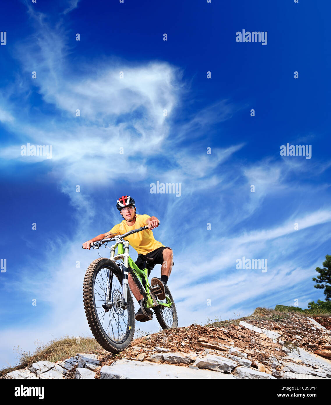 Person riding a mountain bike on a slope - Stock Image