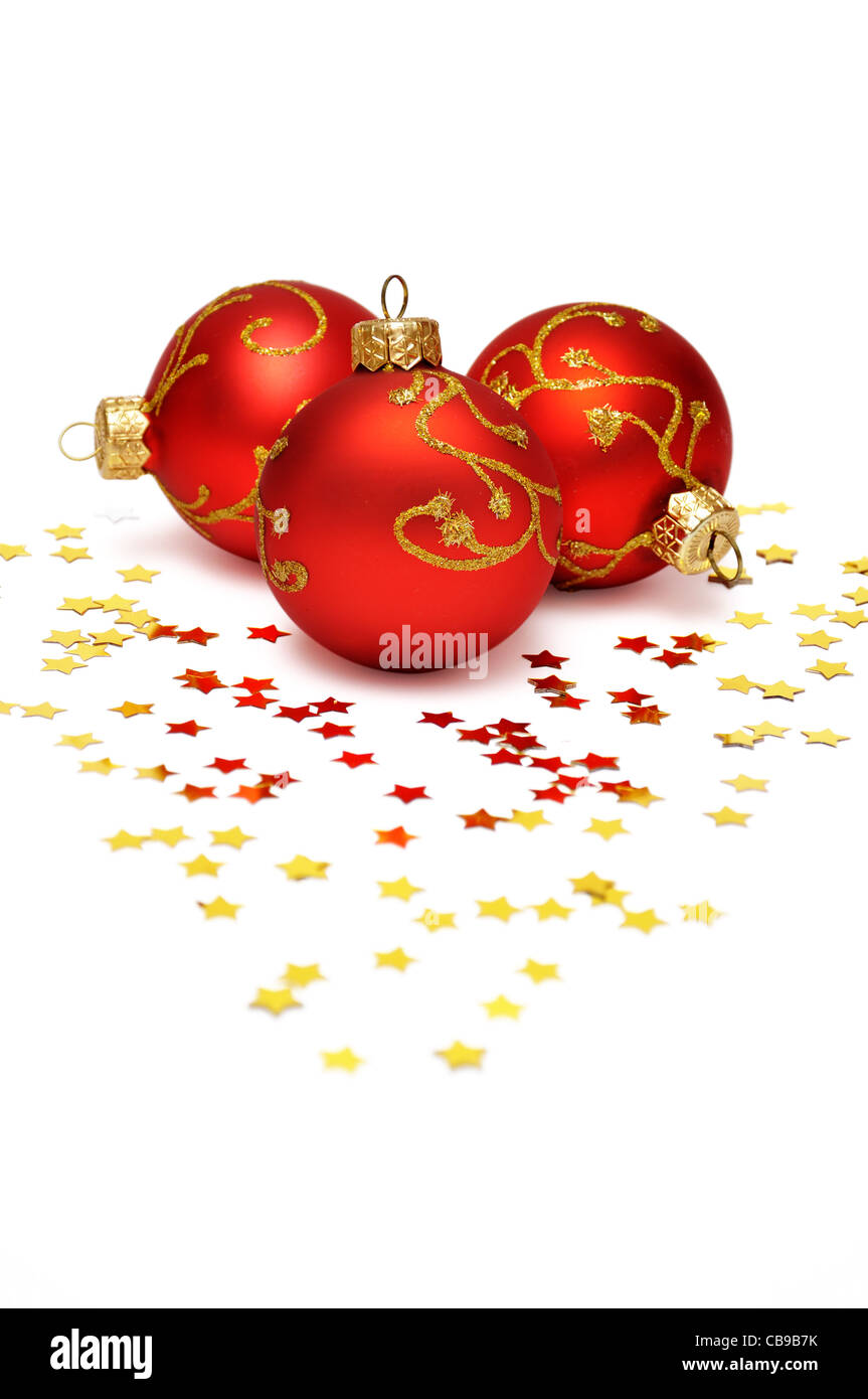 Christmas postcard with three red balls and golden conffeti - Stock Image