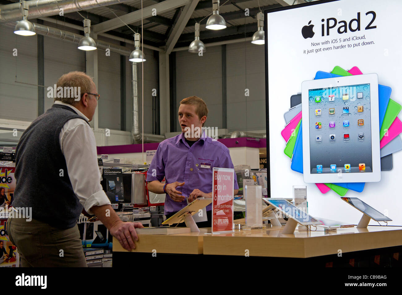 A member of staff at a PC World store demonstrating an Apple IPAD 2 to a customer, UK - Stock Image