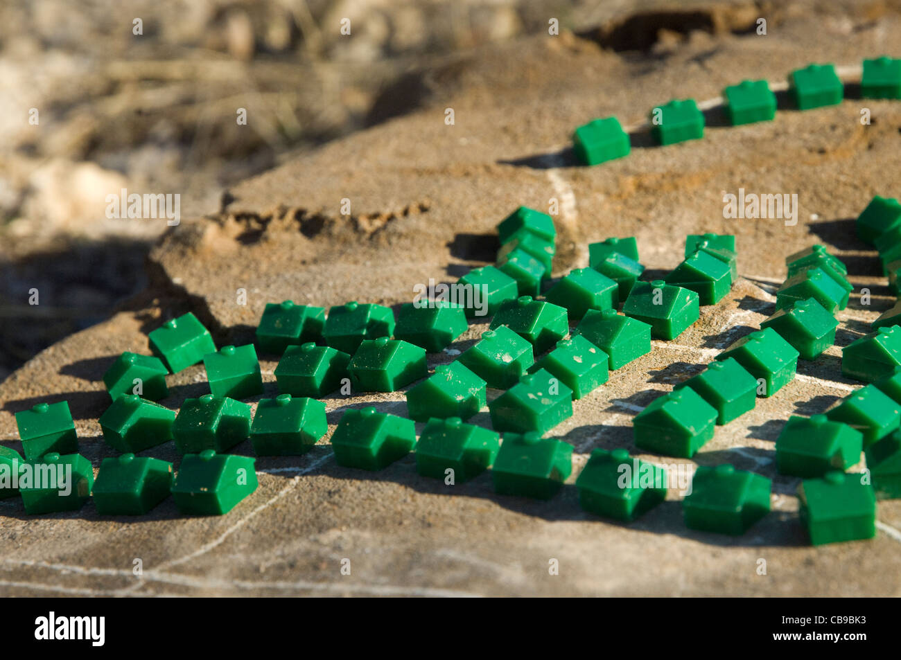 Plastic houses from a board game arranged in 'neighborhoods' in central Texas dirt by a child who's interest is Stock Photo