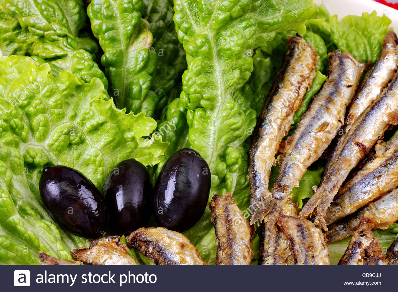 fried anchovies on lettuce leaves with olives - Stock Image