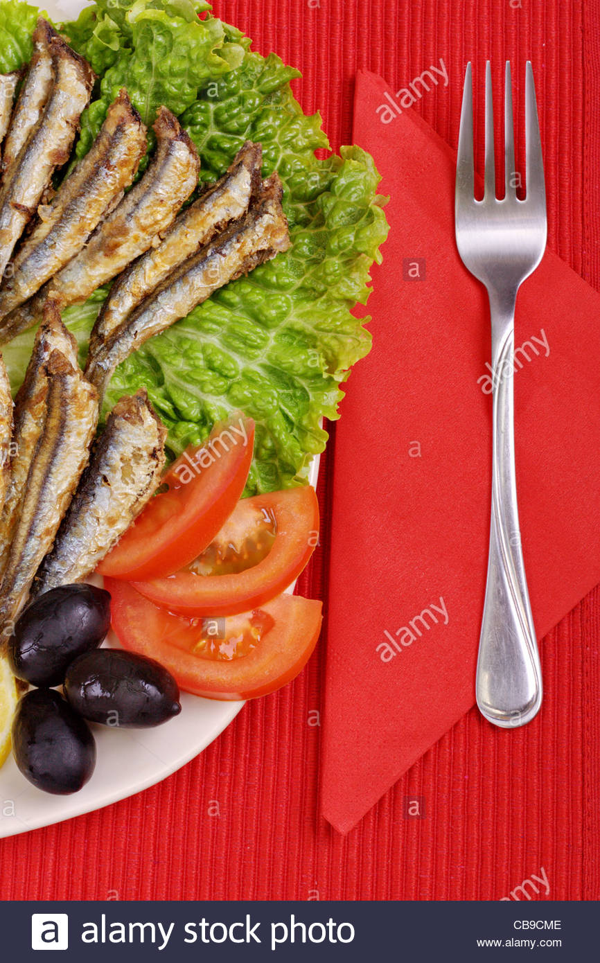fried anchovies on lettuce leaves with lemon, tomatoes and olives - Stock Image