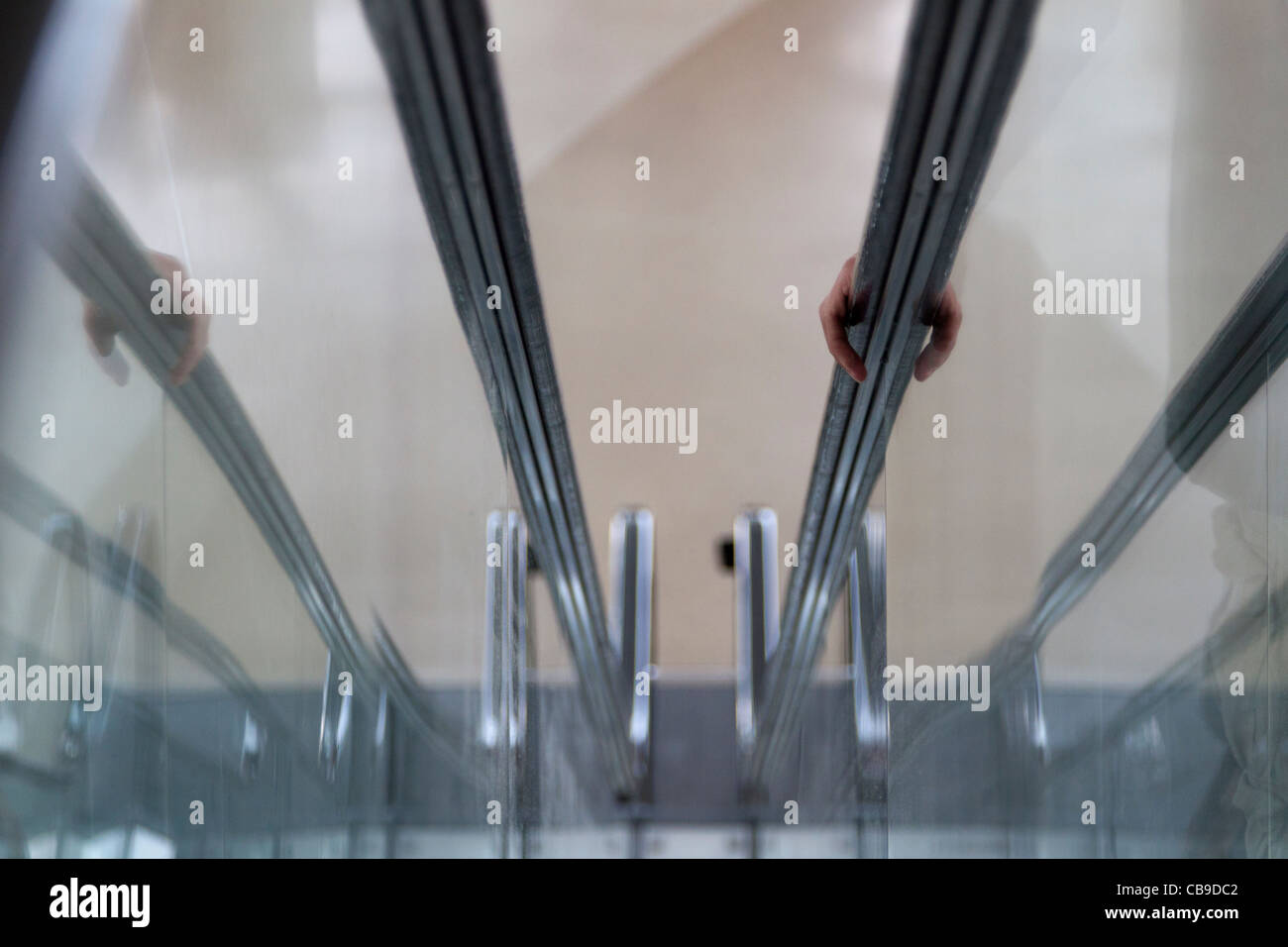 Abstract image of a person riding down an escalator, showing the hand grabbing the handrail and its reflection - Stock Image