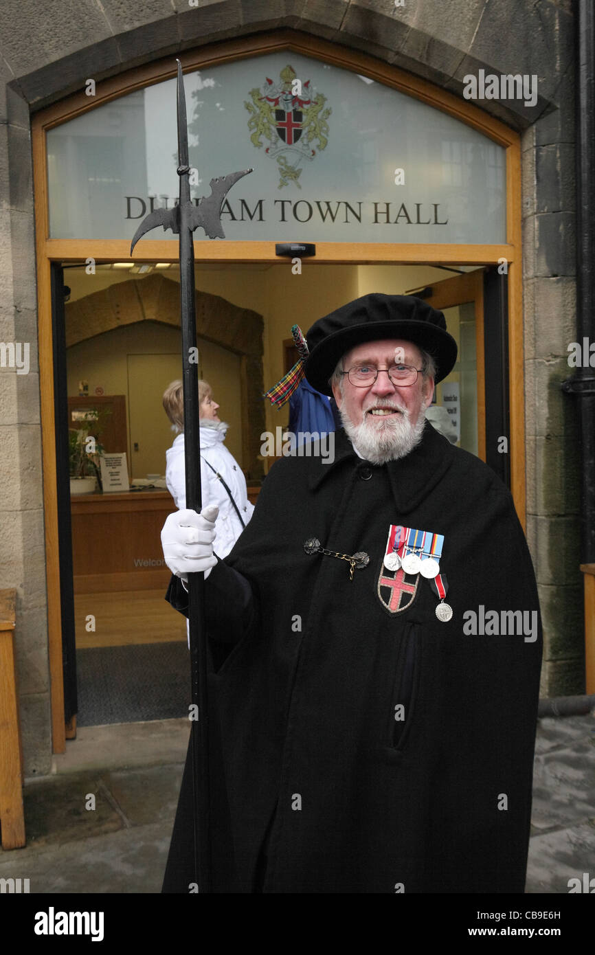 Senior man carrying pike staff and wearing medals at the entrance to Durham town hall, north east England, UK - Stock Image