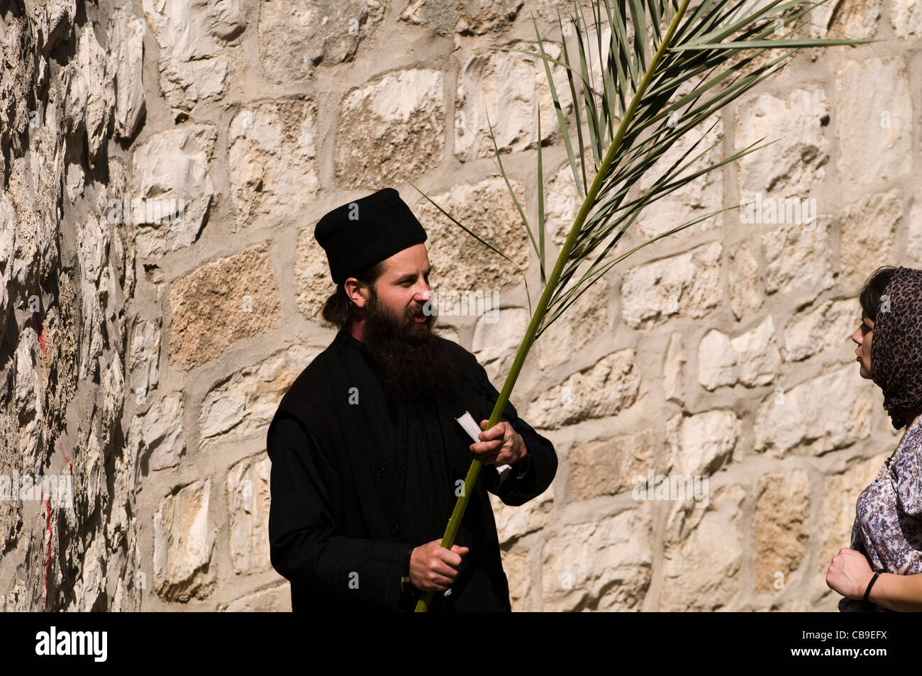 A Russian Orthodox priest holding a palm branch on Palm Sunday day. - Stock Image