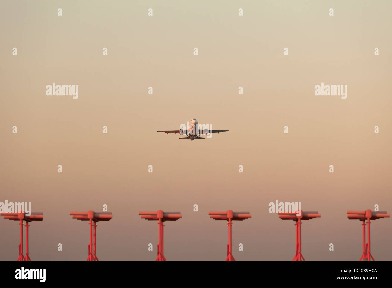Airplane takeoff at sunset - Stock Image