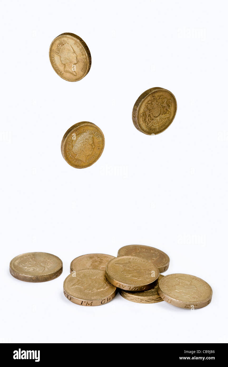 a small pile of british one pound coins isolated on a white background with falling pound coins - Stock Image