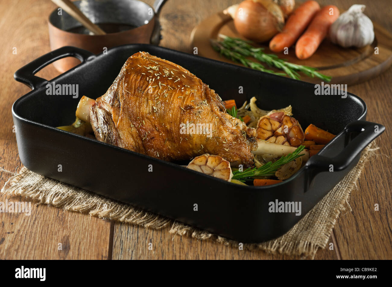 Roast leg of lamb with garlic and rosemary in a roasting tray - Stock Image