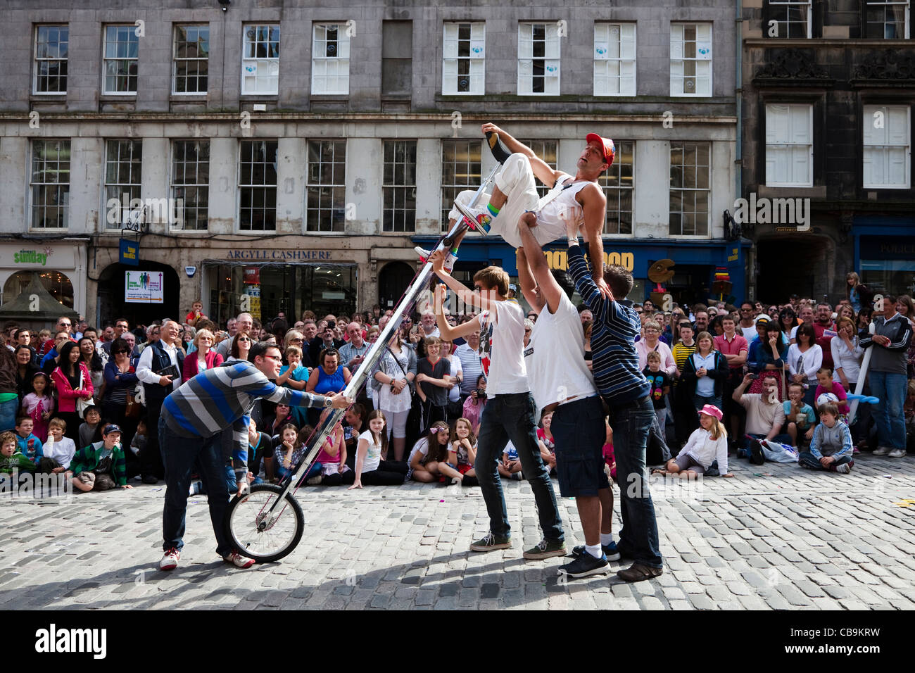 Street actor in High Street, Royal Mile, cycle Edinburgh at the Fringe festival - Stock Image
