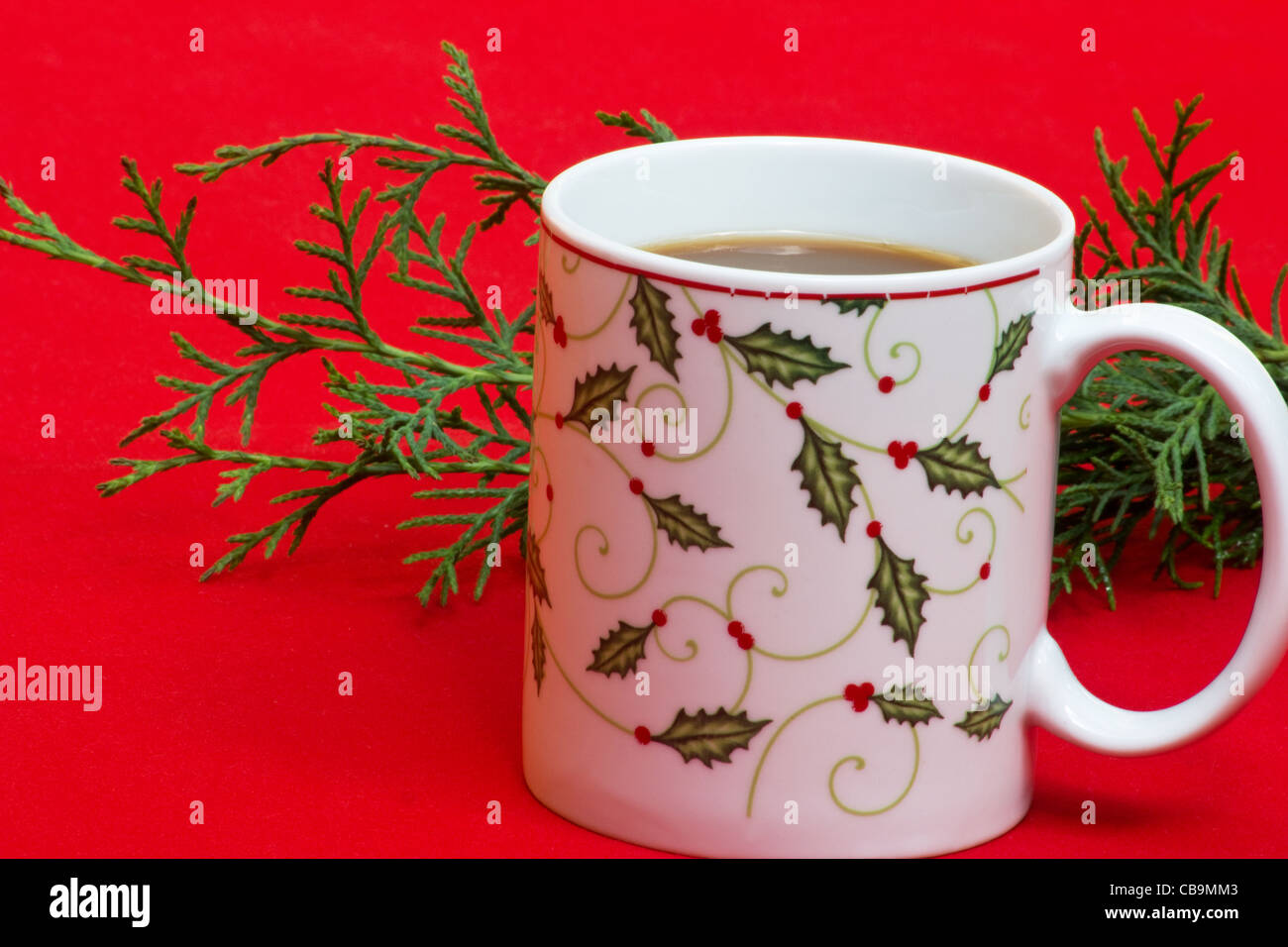 Christmas motif coffee mug and evergreen on red background - Stock Image
