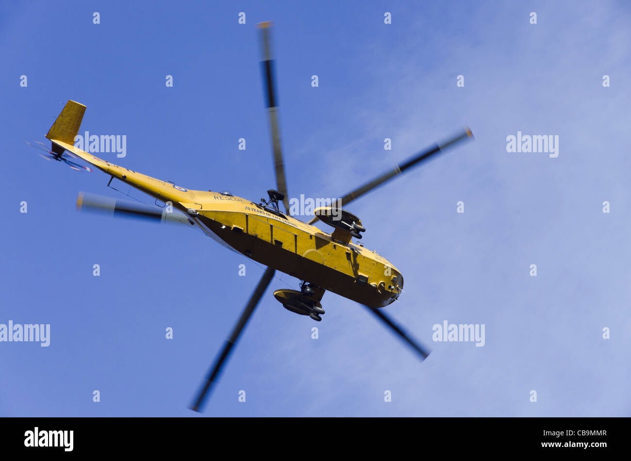 North Wales UK RAF Sea King HAR3A search and rescue helicopter flying in a blue sky from below - Stock Image