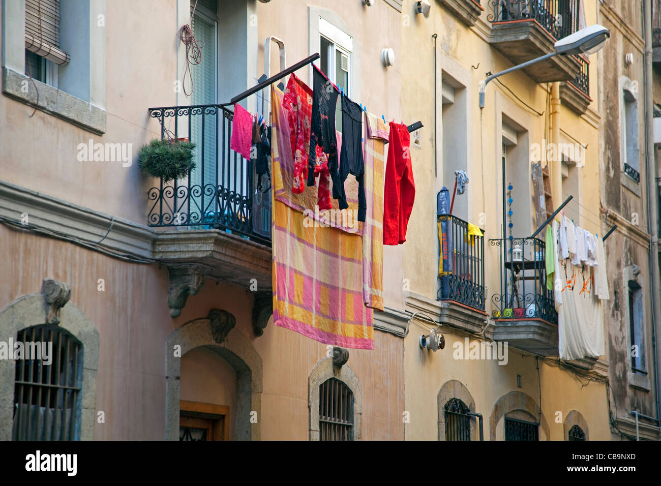 Laundry drying from balcony in the La Barceloneta quarter in Barcelona, Spain - Stock Image