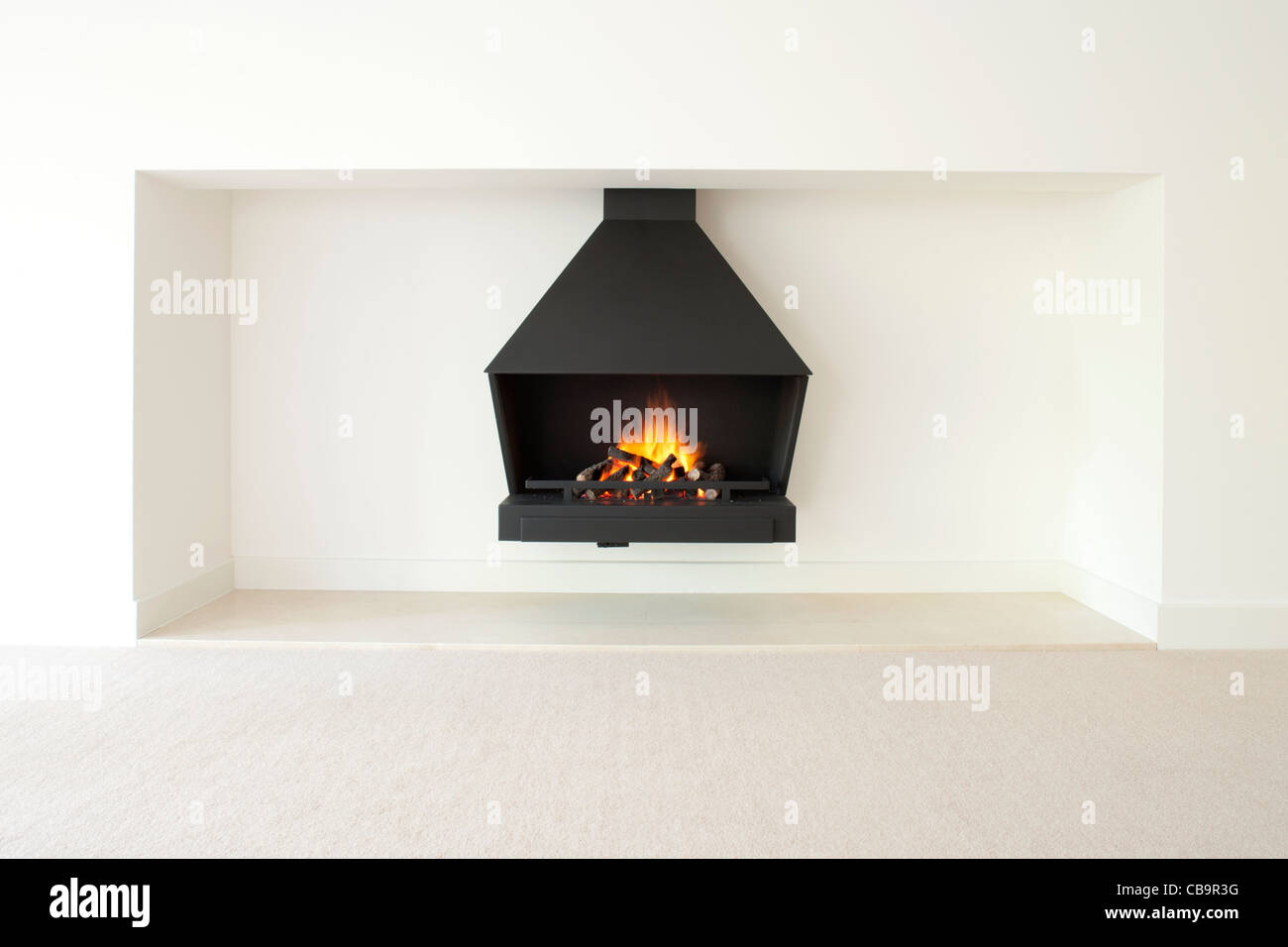 Modern burning gas fire with logs - Stock Image