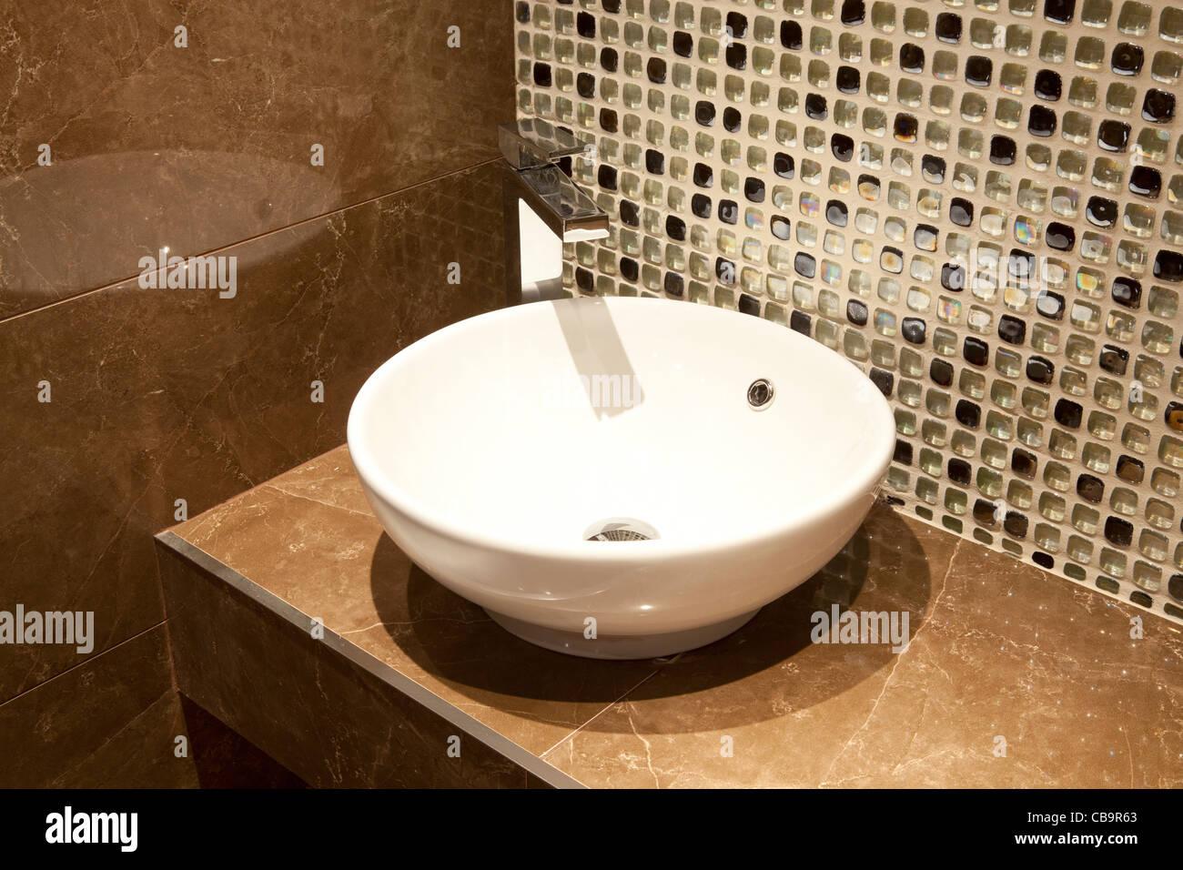 Circular white ceramic hand-basin in modern cloakroom - Stock Image