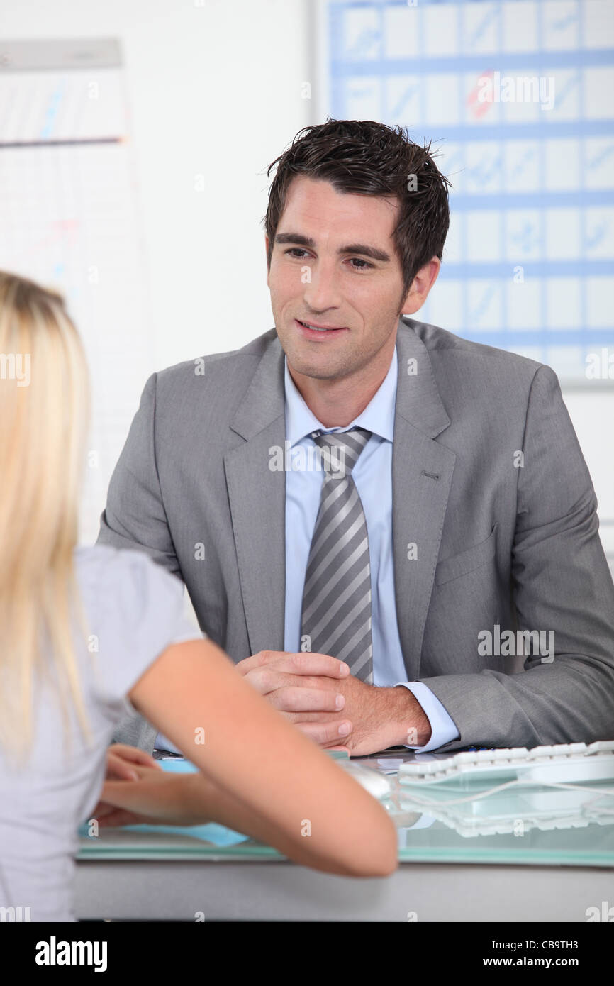 Man sat at desk talking to blond female - Stock Image