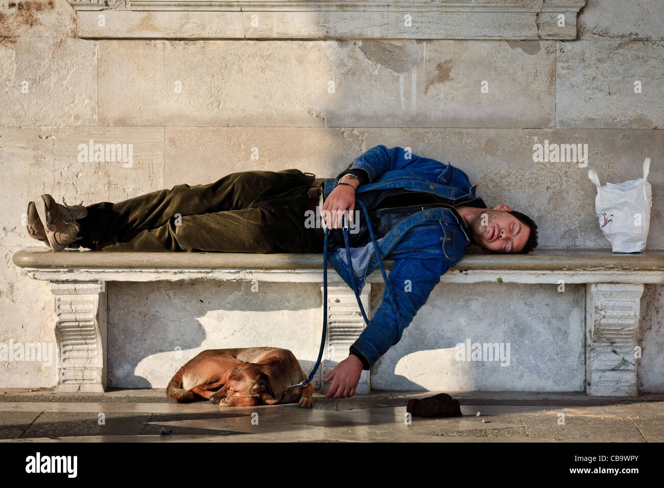 Homeless man with his dog asleep on a bench in Venice, Italy - Stock Image