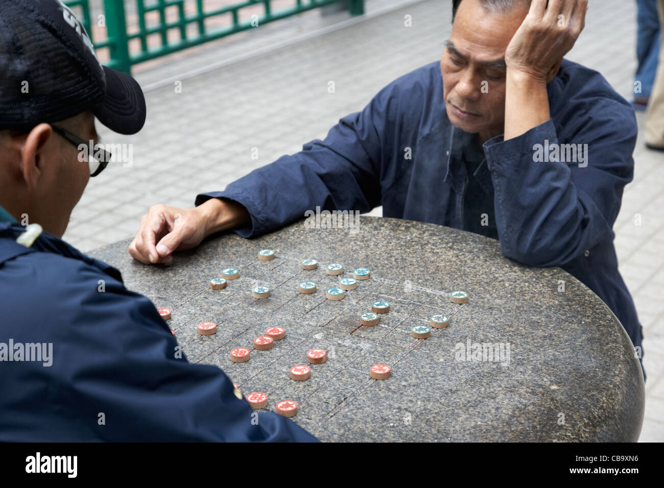 two chinese men playing xiangqi chinese chess on an outdoor board in a park hong kong hksar china - Stock Image