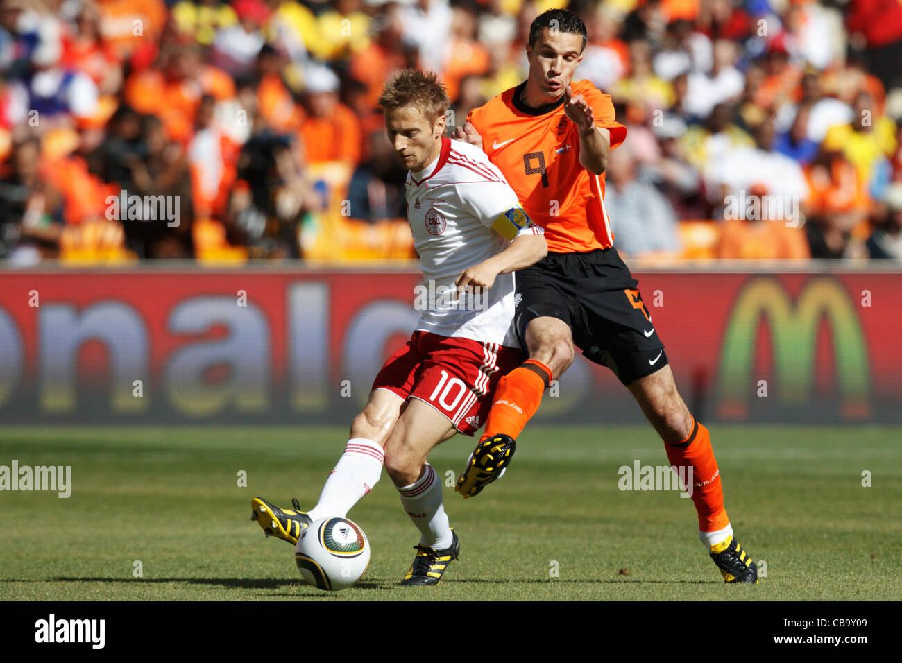Robin van Persie of the Netherlands (R) pressures Denmark team captain Martin Jorgensen (L) during a 2010 World - Stock Image