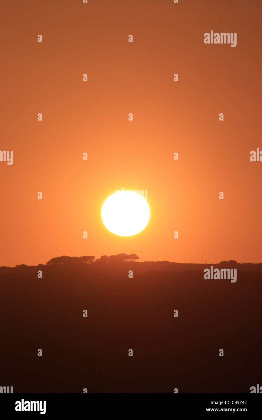 Sun set with trees on the horizon and a nice red orange sky Stock Photo