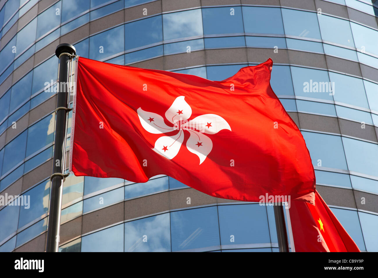 hong kong flag flying in front of office building exchange square hong kong hksar china - Stock Image