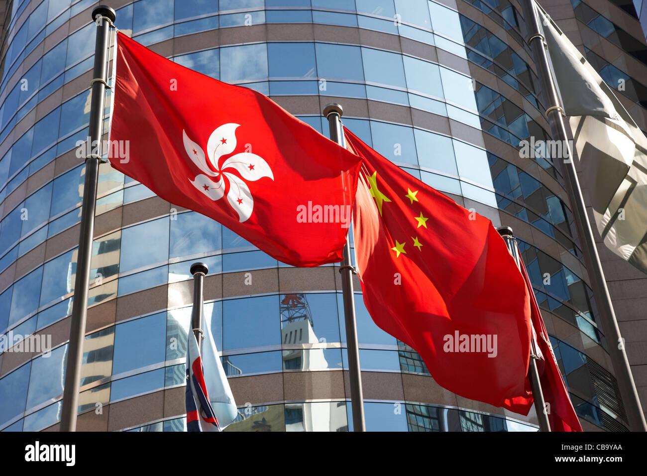 chinese and hong kong flags flying in front of stock exchange building hong kong hksar china - Stock Image