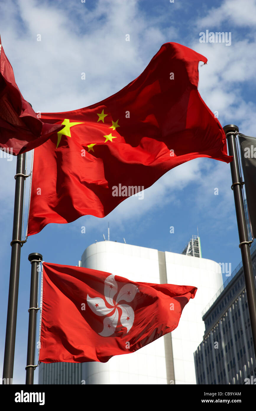 chinese and hong kong flags flying hong kong hksar china - Stock Image