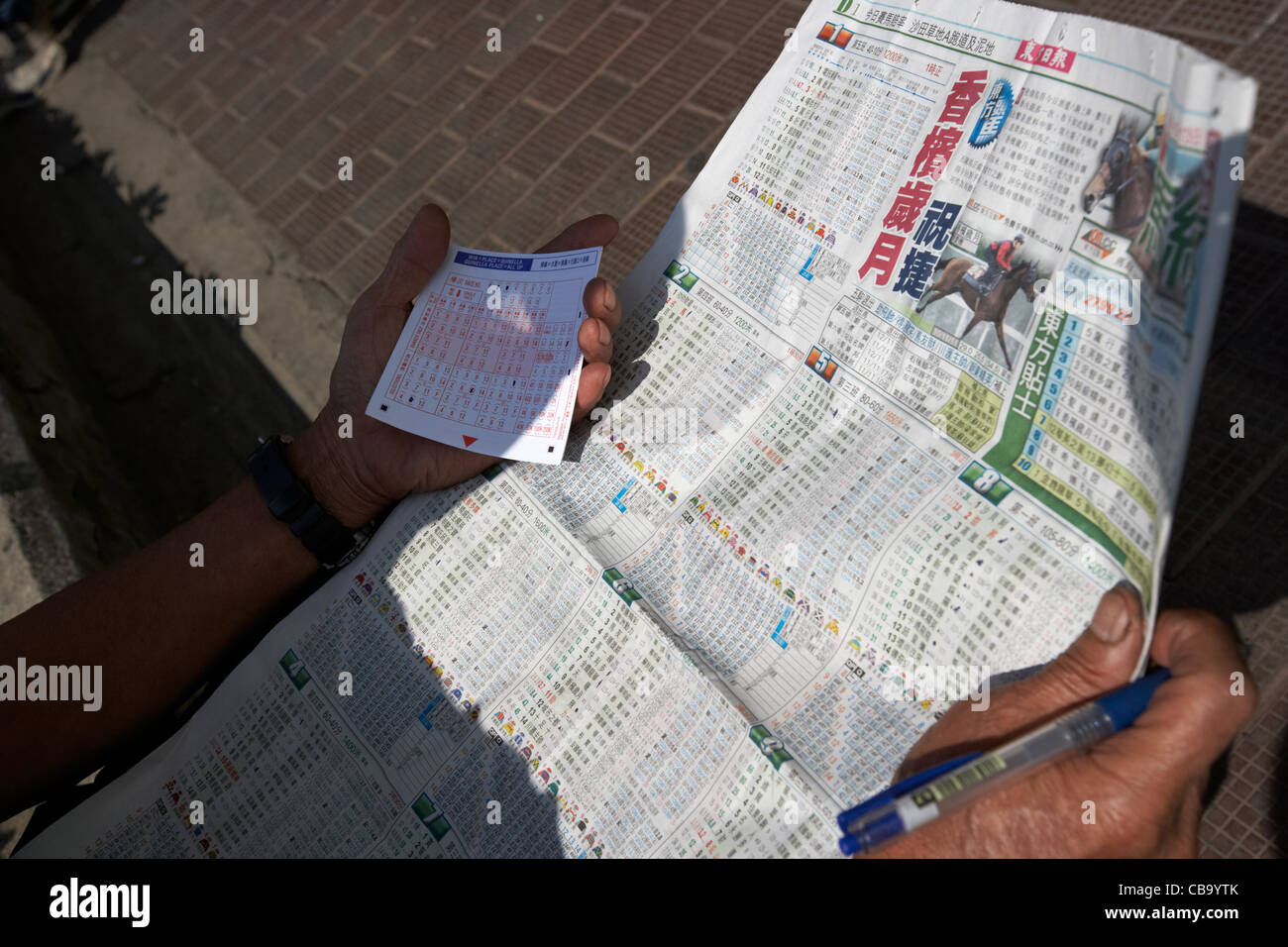 chinese man with betting slip and newspaper with horse
