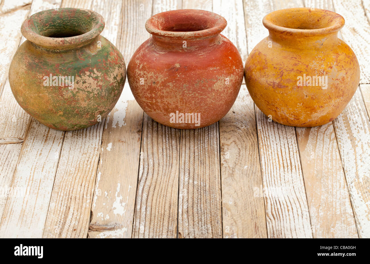 three small clay plant pots (mass produced planter) with rough, grunge finish, on white rustic wood background - Stock Image