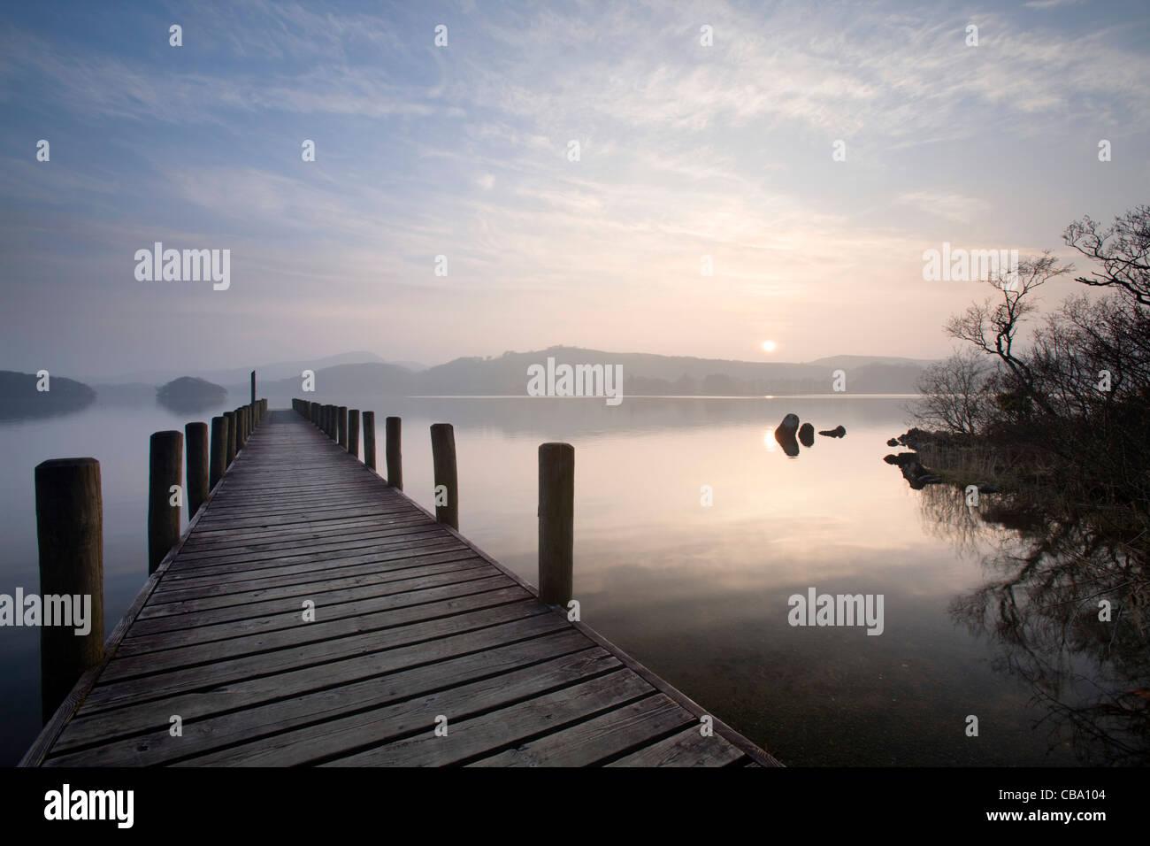 Jetty into still lake Lake district - Stock Image