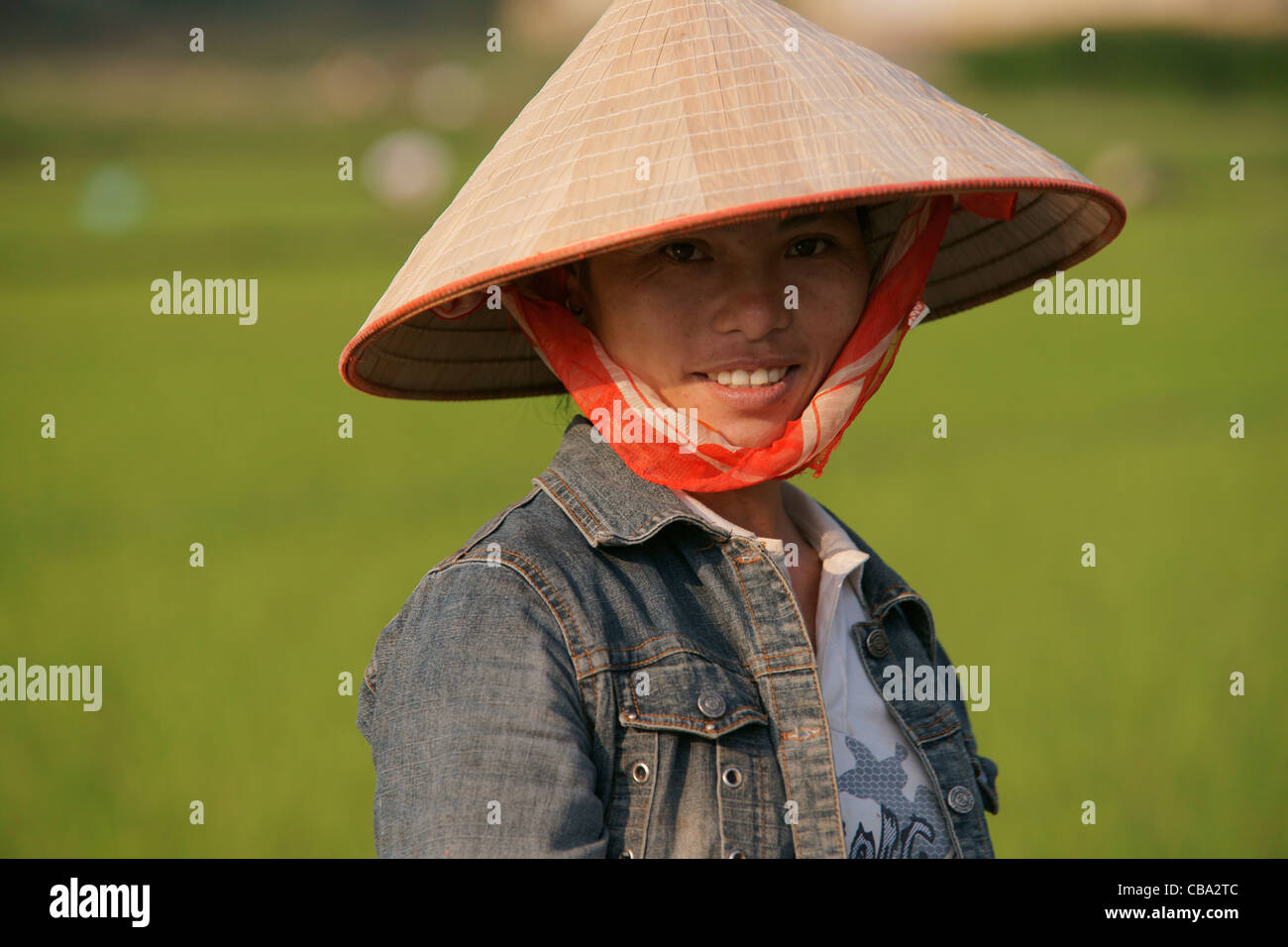 Vietnamese woman working in rice paddy with Vietnamese conical sedge hat -  Stock Image 7b17db00cea